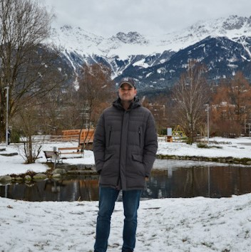 Justin, a white man, standing in front of snowy mountains in Innsbruck