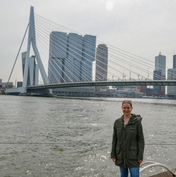 Sarah, a white woman, standing in front of a bridge and modern skyscrapers in Rotterdam